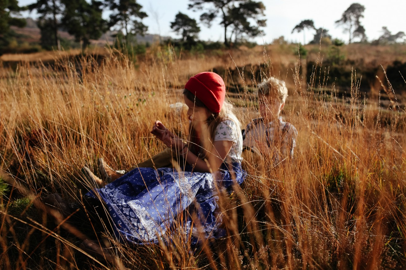 Bonnets for winter in long grass; Childrens portrait photographer in London, Surrey and Kent London Children Photography